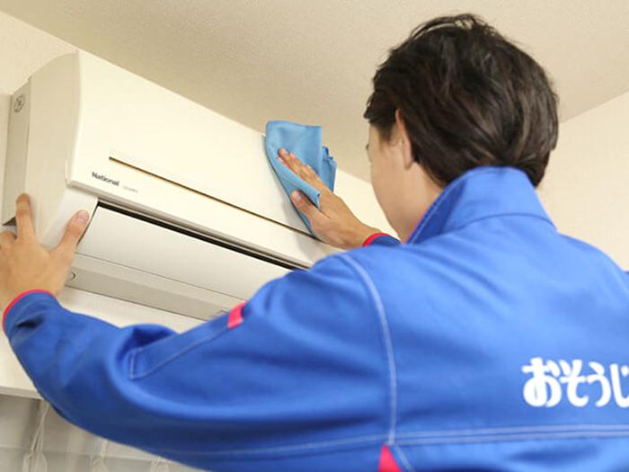 エアコンを拭く男性